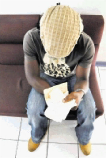 SHREDDED: Ramsy Tambong Ning with his torn passport. 16/12/08. Pic. Vathiswa Ruselo. © Sowetan.