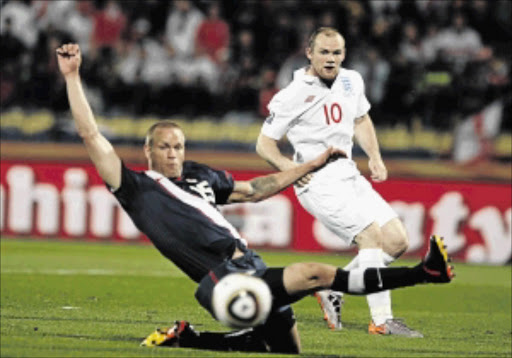 CLASS ACT: England's Wayne Rooney, right, is challenged by US defender Jay DeMerit. Rooney will take over from Steven Gerrard as England skipper Photo:  James Oatway