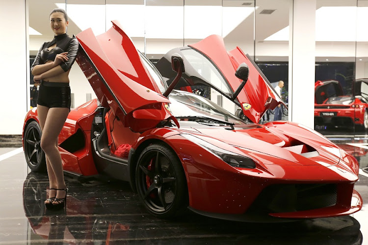 A model poses beside a Ferrari LaFerrari hybrid sports car at a Dream Car Show in Beijing, China. The Chinese Ministry of Finance has raised the tax on 'supercars' and other luxury goods. Picture: EPA/WU HONG