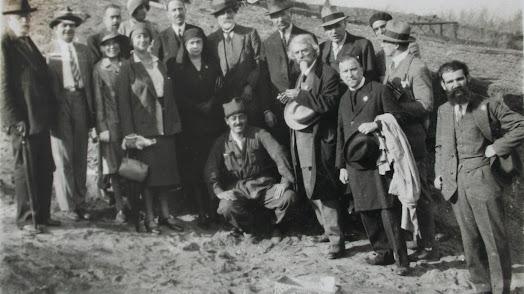 El arqueólogo belga con barba blanca junto a un grupo de intelectuales en una vista a una excavación.
