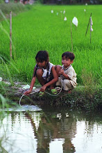 Photo: Kids drink water thru' pipe in the fertile Mekong Delta region