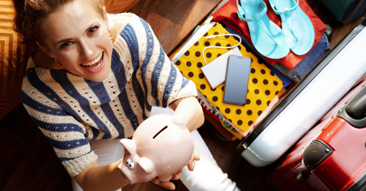 A woman next to a suitcase and holding a piggy bank in her hand