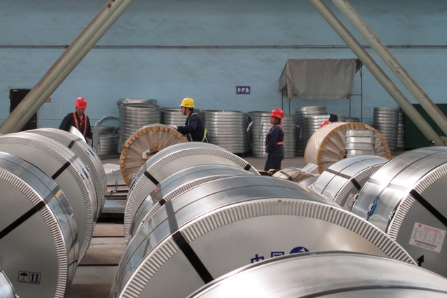 Workers pack cold rolled steel coil at a steel company.