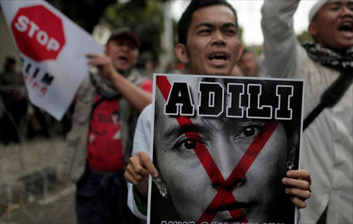 "A protester holds a poster with a defaced image of Nobel Peace Prize winner Aung San Suu Kyi in front of the Myanmar embassy in Jakarta, Indonesia November 25, 2016. The text on the poster reads, ""Bring Aung San Suu Kyi to the court""."