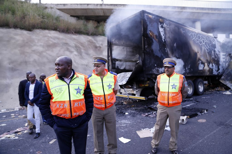 KZN MEC for Transport, Community Safety and Liaison Mxolisi Kaunda, with Road Traffic Inspectorate (RTI) officials, inspects the area on April 30 2018 where trucks were set alight at Mooi River Toll Plaza on the N3.