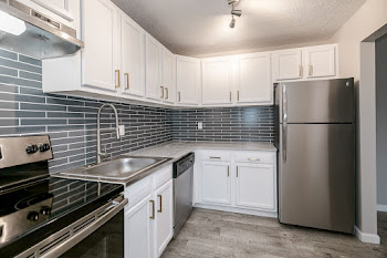 The Beverly floorplan's fully-equipped kitchen with a tile backsplash, white cabinets, and stainless steel appliances
