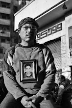 Photo: A man wears a framed photo of his martyred son around his neck.