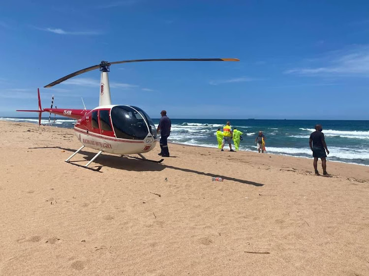 Rescue personnel on La Mercy Beach, north of Durban, on Friday after a father, his son and their dog drowned while swimming.