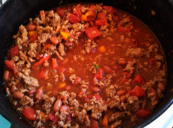 Add tomatoes and beans (no need to drain cans), and wine.  Stir. ...