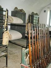Photo: grote slaapzaal met stapelbedden tijdens WOII :    geweren stonden klaar voor actie