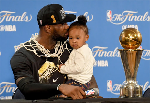 LeBron James #23 of the Cleveland Cavaliers kisses his daughter Zhuri during a press conference after defeating the Golden State Warriors 93-89 in Game 7 to win the 2016 NBA Finals at ORACLE Arena on June 19, 2016 in Oakland, California. Picture Credit: Getty Images