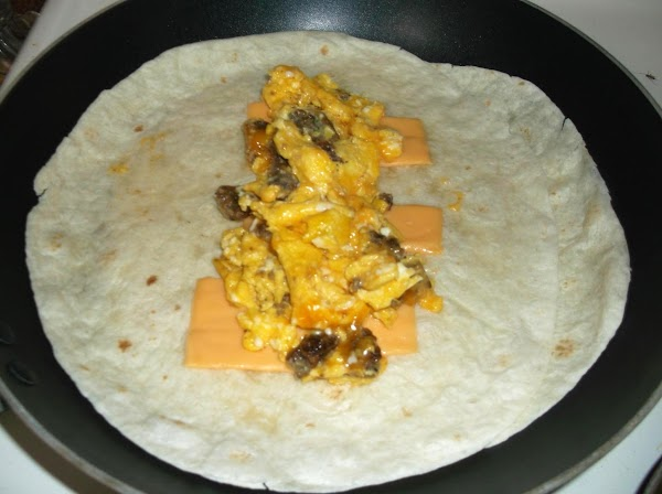 Spoon half of the egg mixture down the middle of each tortilla; fold bottom...