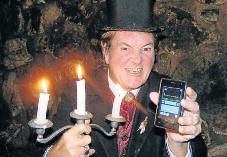Mystery Ghost Bus tour host Mark Rose-Christie shows the cellphone version of the Spirit Box for the tour