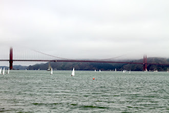 Photo: The USA 76 America's Cup boat with full carbon rig (the gray boat under the bridge) can be seen chartered in the bay alongside the Lasers.