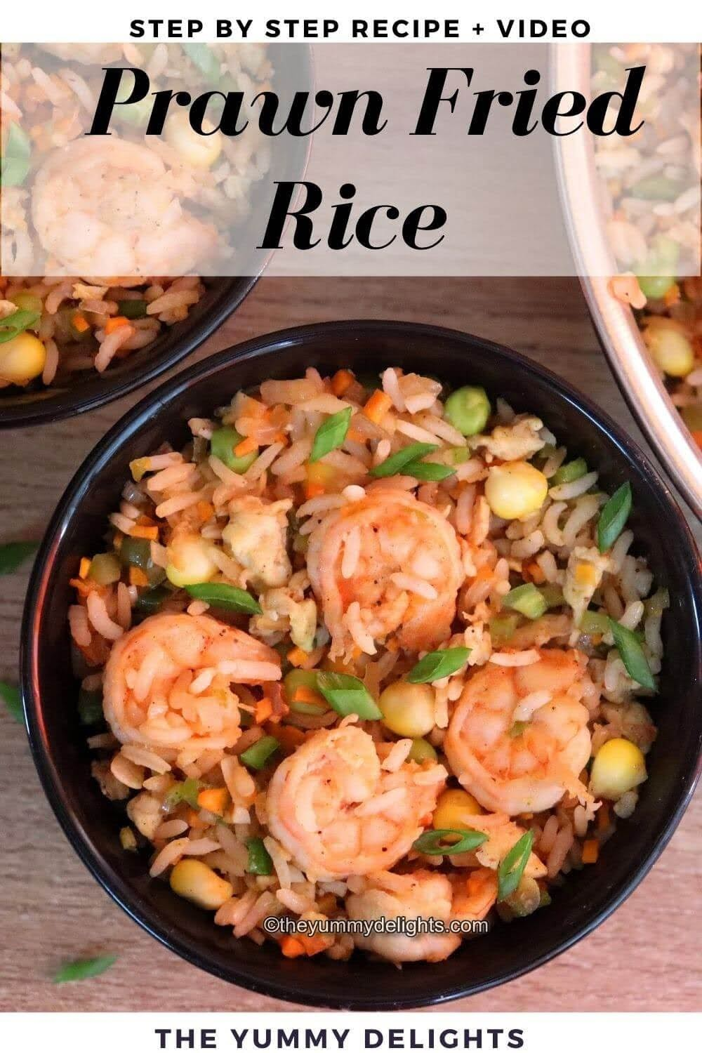 prawn fried rice served in a black bowl. Fried rice is garnished with spring onion greens.