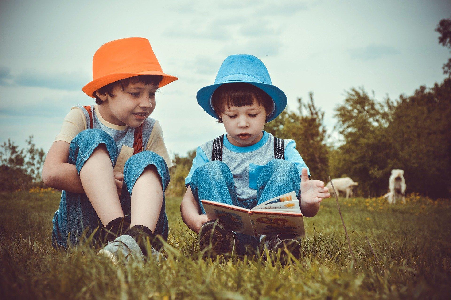 Two kids in a field reading.