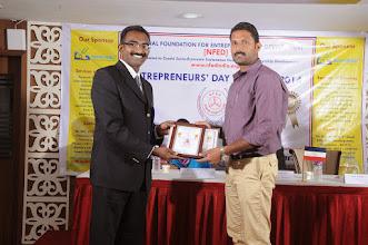 Photo: Guest of Honour Mr. Bobby A. Mathew Issuing Young Entrepreneur Award to Mr. P. Shanmugha Raja, Director, Sri Venkateswara Bus Service, Salem