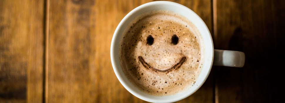 a cup of coffee with a smiling face in the froth