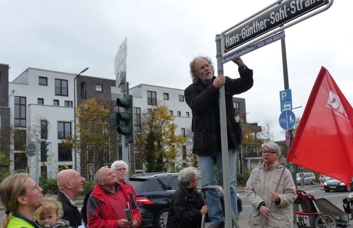 DKP-Delegation am Straßenschild. Uwe Koopmann bringt Zusatzinformation an.