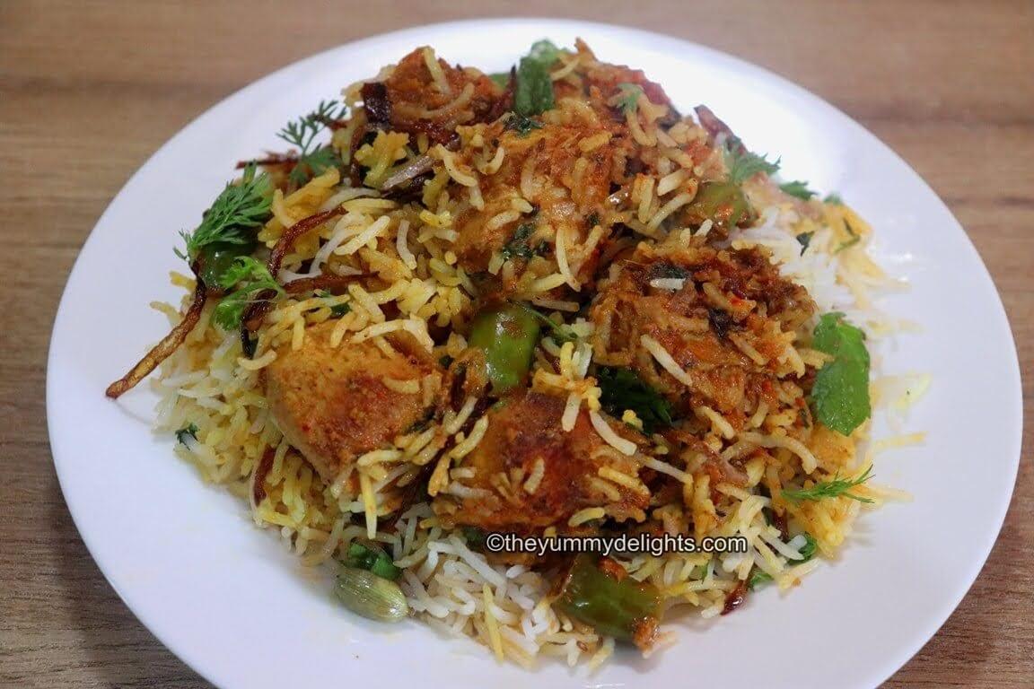 chicken tikka biryani served in a white bowl. Garnished with coriander leaves.