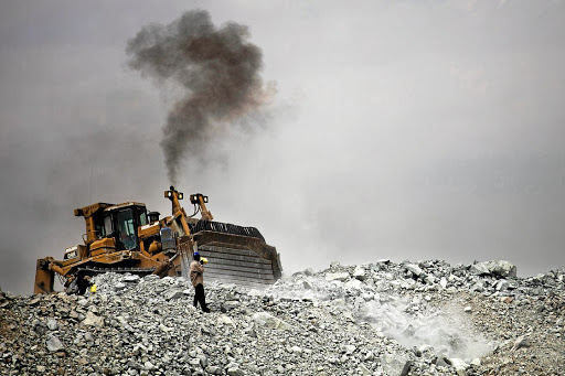 High-risk, high-reward: A bulldozer moves rubble as a villager searches for gold contained in discarded waste rock from the North Mara mine operated by African Barrick Gold in Nyangoto, Tanzania. Picture: BLOOMBERG/TREVOR SNAPP