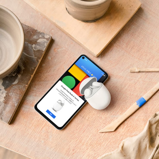 雑然とした陶芸工房の作業台の上にある開いた状態の充電ケースに収められた Google Pixel Buds A-Series と、その横に並んで置かれた 5G 版 Google Pixel 4a。