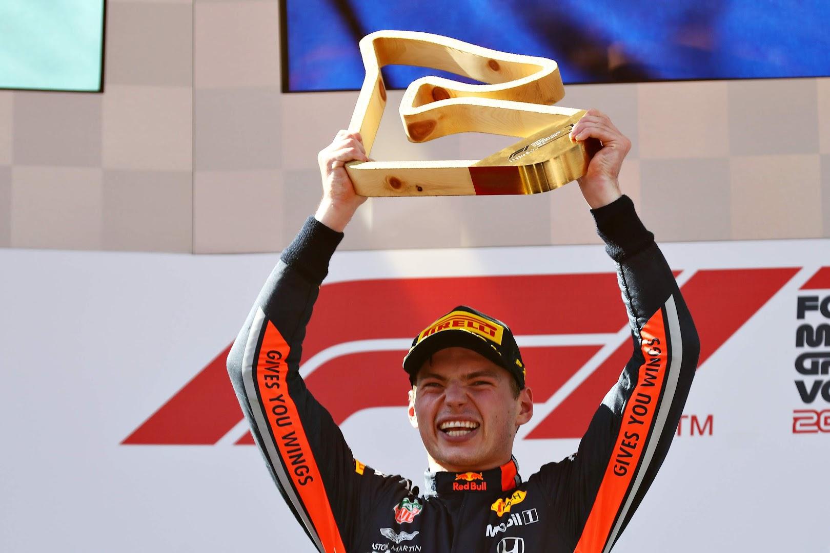 F1第9戦オーストリアGP表彰台でトロフィーを掲げる笑顔のフェルスタッペン