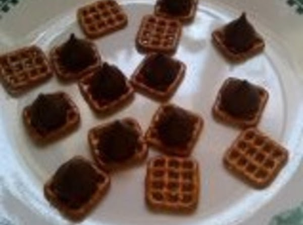 Place pretzels on a microwavable plate.   Place an unwrapped Hershey's kiss on...