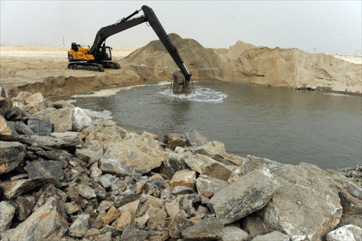 A caterpillar digs reclaimed land from the sea, on January 31, 2013 in Lagos, during the building of the three and a half kilometre long sea defence barrier called