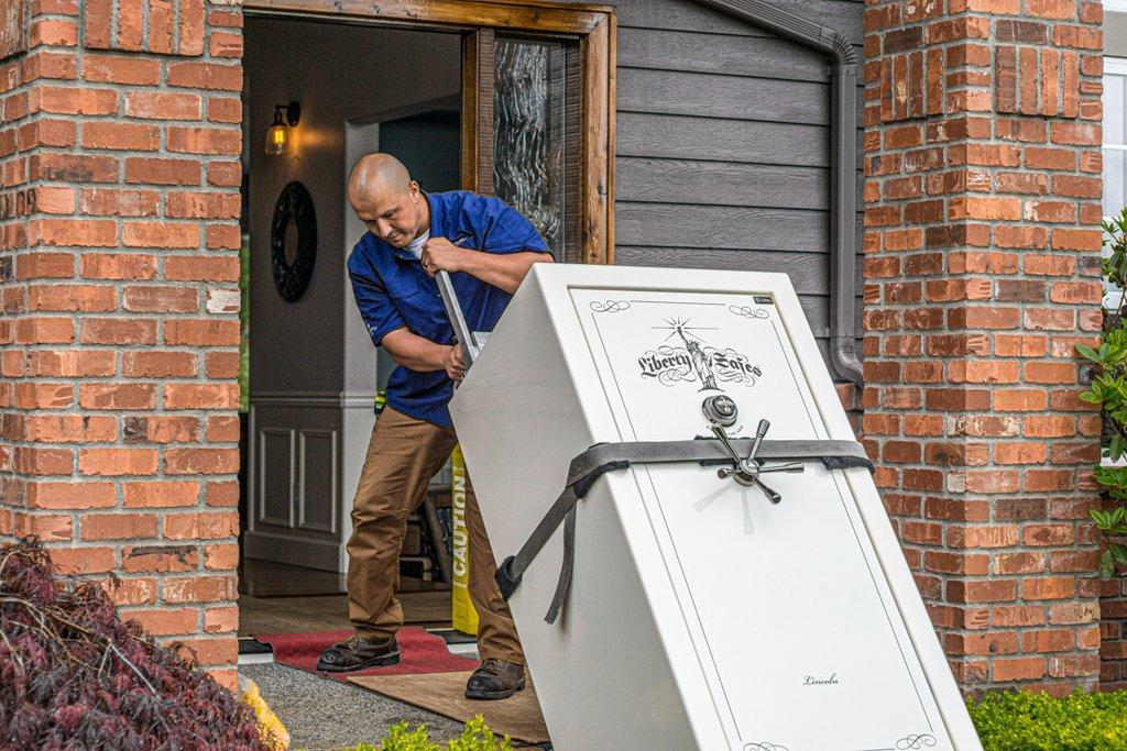 a man dragging a gun safe into house