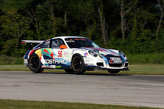 Photo: GT3 Cup Porsche leaps off the ground over hump in roadway, where the two race courses connect at Autobahn, Grand Prix, near Joliet IL.
