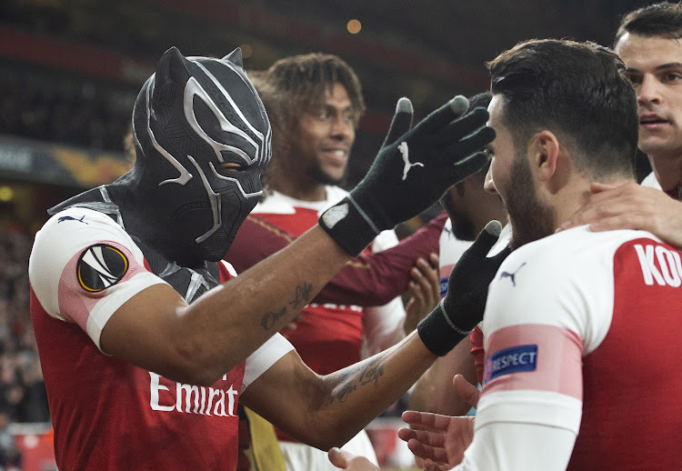 Pierre-Emerick Aubameyang of Arsenal celebrates his second goal by wearing a mask of the Marvel Comics character the Black Panther during the UEFA Europa League Round of 16 Second Leg match between Arsenal and Stade Rennais at Emirates Stadium on March 14, 2019 in London, England.