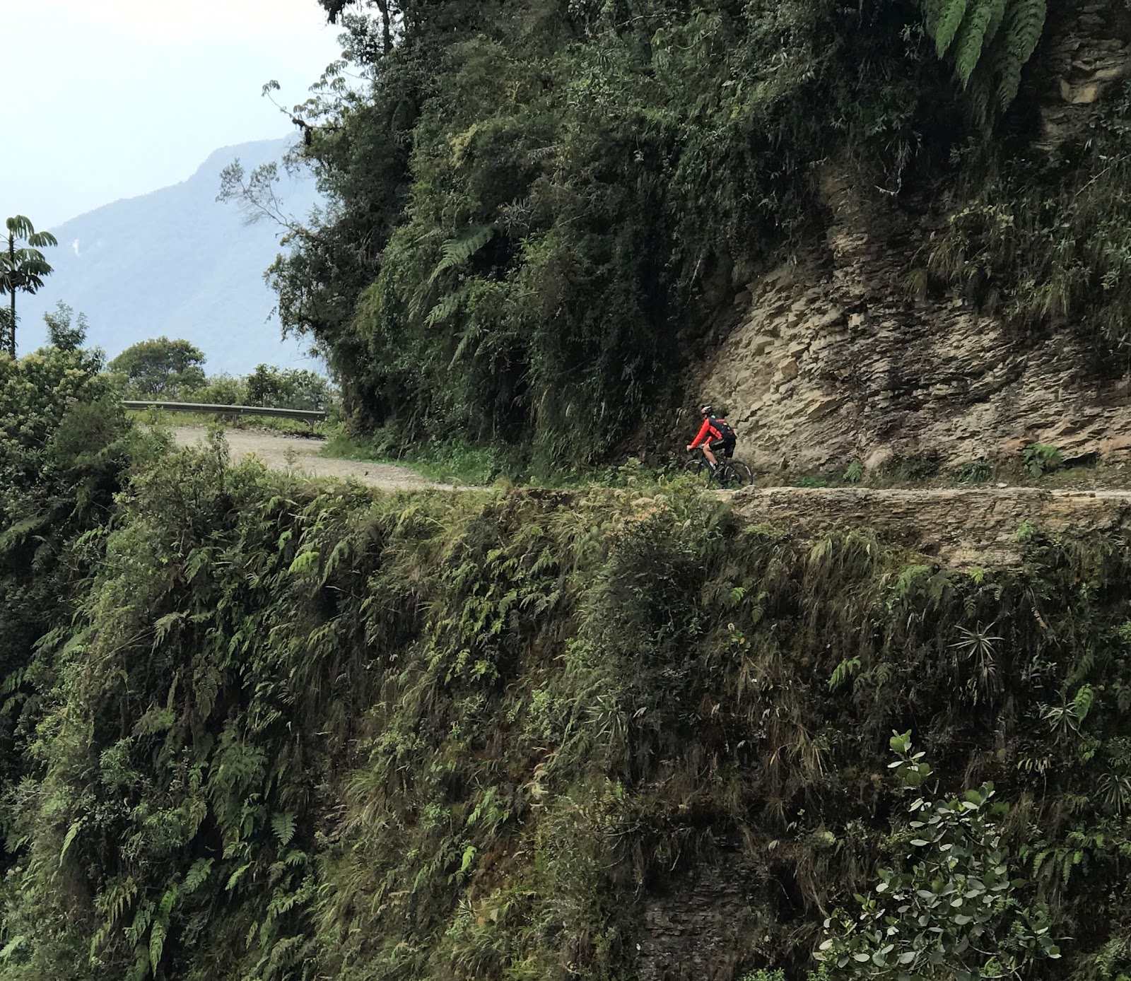 Bicyclist riding along narrow road with cliff on Death Road