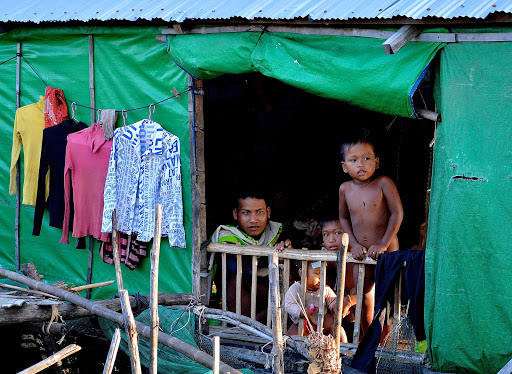 vietnam-house-green-siding.jpg - Family members peer out of a fairly typical house with green siding and tin roof in a rural part of Vietnam.