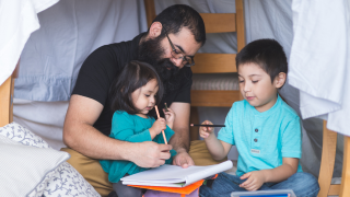 man holding young girl with young boy next to him drawing