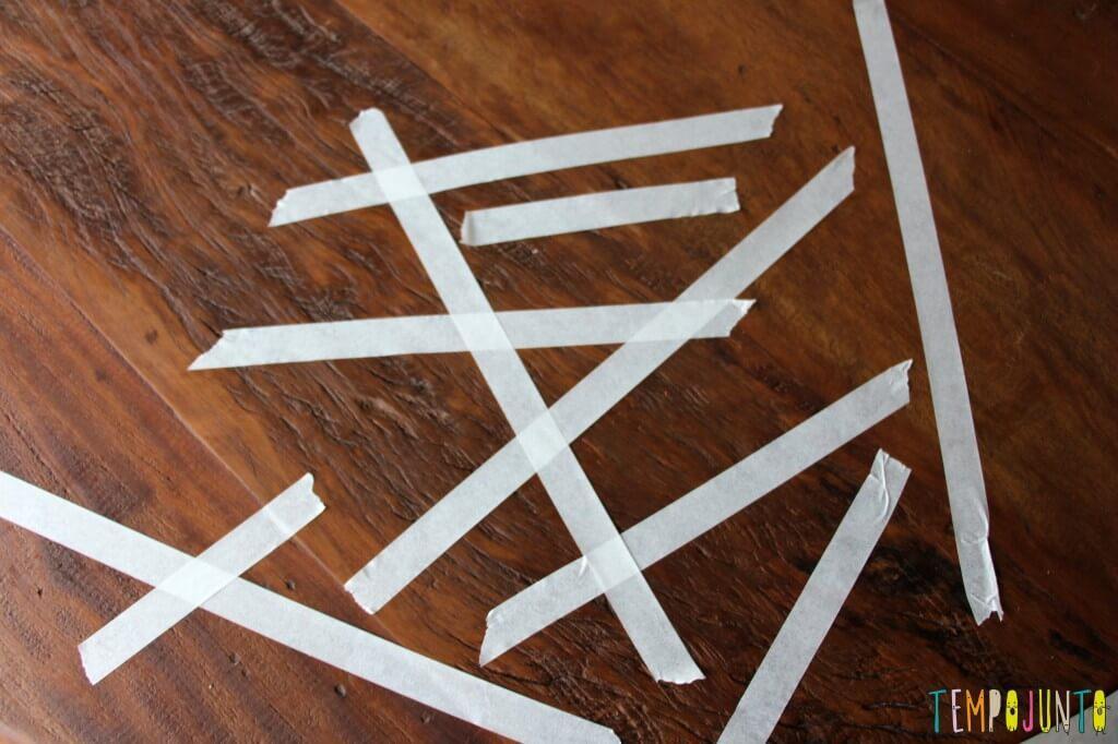 Pedaços de fita crepe para para a criança pequena retirar e estimular a coordenação motora fina.