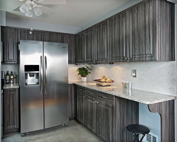 Stainless Steel Side-by-Side French Door Fridge in a Kitchen with Black and Gray Cabinets