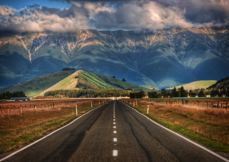 """Photo: The Long Road to New Zealand  This is one of countless beautiful roads that crisscross New Zealand. I'm afraid I've forgotten exactly where I was when I took this photo! I know that is very lame, but I bet people around here can help me pinpoint the area. As far as the camera settings, this is the kind of shot you can get with something called """"compression,"""" a method where you use a zoom lens and zoom in quite far. It takes images in the distance and makes them larger than life."""