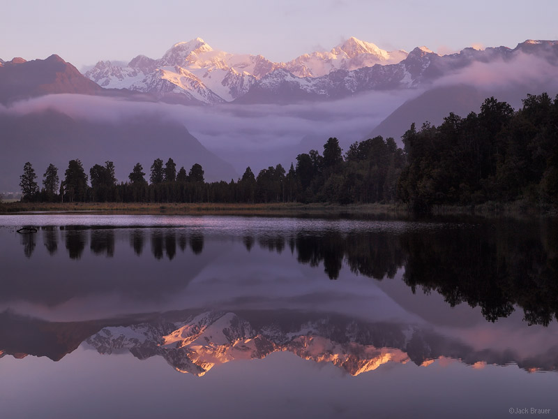 Photo: Sunset reflection of Mt. Tasman and Mt. Cook, as seen from Lake Matheson on the West Coast near the town of Fox Glacier. Photo © copyright by Jack Brauer.