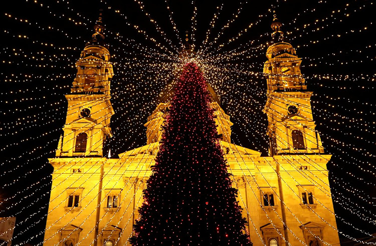 A Christmas tree is lit in front of St. Stephen's Basilica in Budapest.