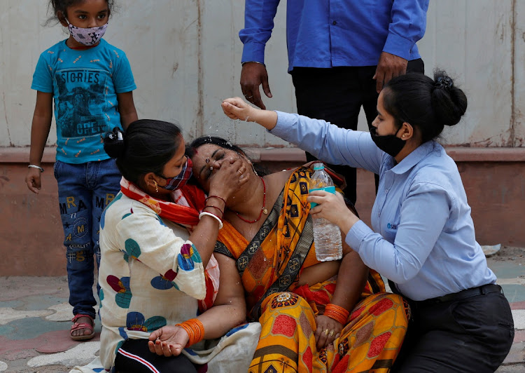 A woman is consoled after her husband died due after contracting Covid-19, in New Delhi, India, April 15 2021. Picture: REUTERS/DANISH SIDDIQUI