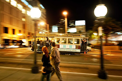 A cable car passes through Union Square in San Francisco at dusk.