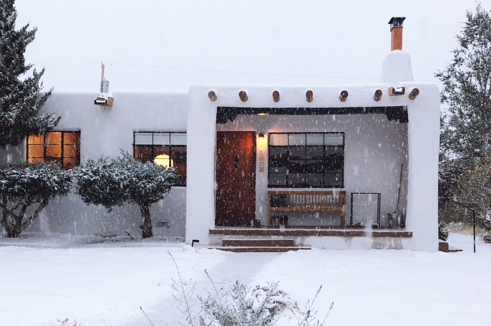 Anna Dorfman's mid-century pueblo revival-style house in Santa Fe, New Mexico, covered in snow.