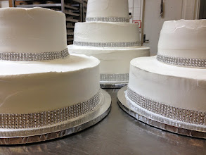 Photo: 3-tier wedding cake w/two 2-tier side cakes all totally smooth white frosting w/silver diamond wrap.