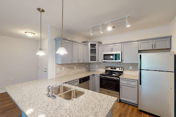 Kitchen with grey cabinets, speckled countertops, and stainless steel appliances