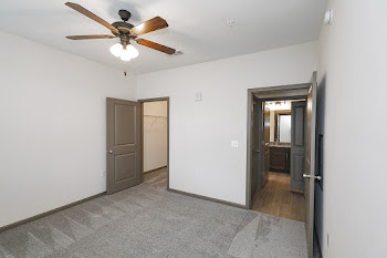 Bedroom with grey carpet, walk in closet, and door showing bathroom across the hall