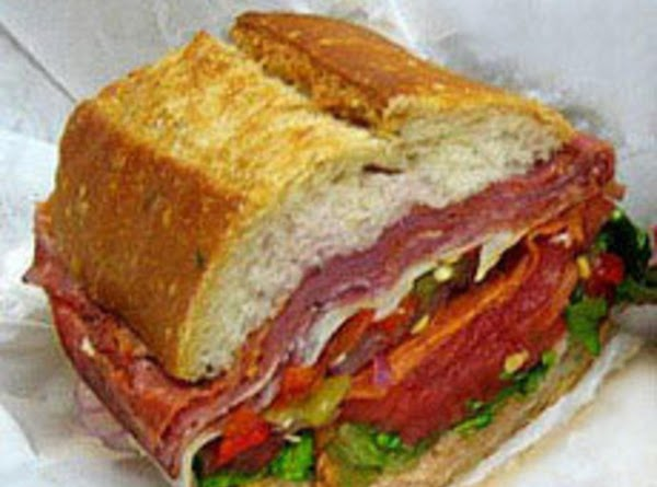 Slice in quarters and serve.    Always serve the Muffuletta Sandwich at...