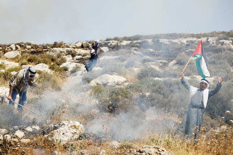 Palestinian demonstrators try to put out a fire caused by tear gas canisters thrown by Israeli forces at a grass field during a protest against Israeli settlements, in Beit Dajan in the Israeli-occupied West Bank April 30, 2021.