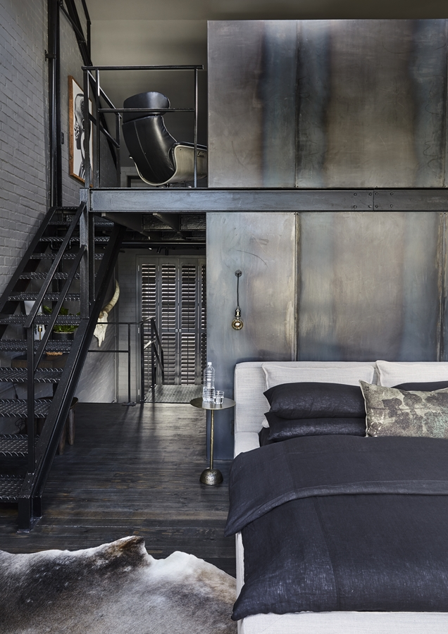 Raw steel panelling divides the bedroom from the ensuite bathroom.