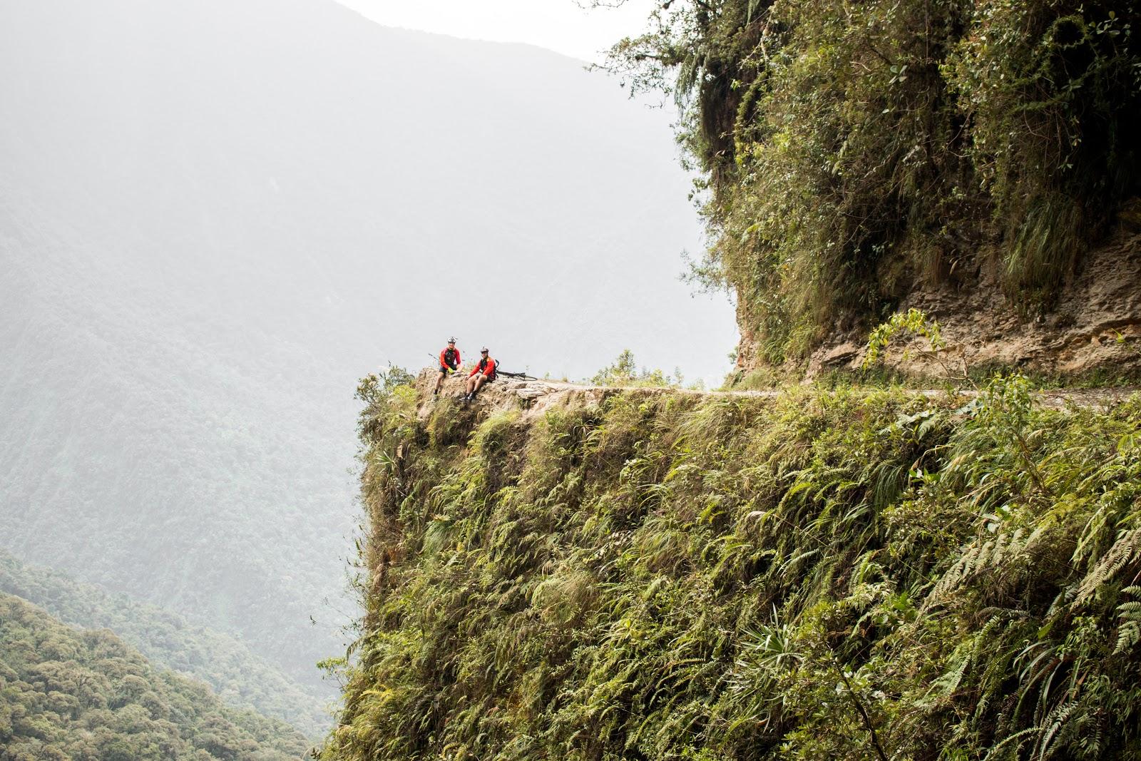 2 cyclists sitting on cliff on Death Road Bolivia Postcard Corner
